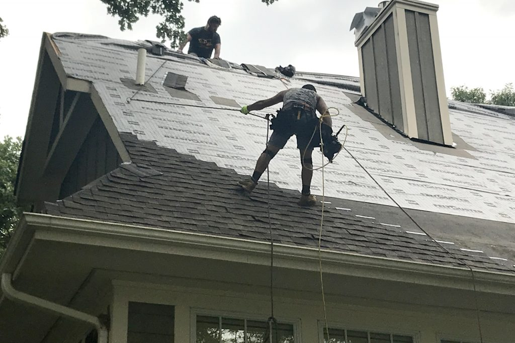 Two Men working on steep roof add new shingles