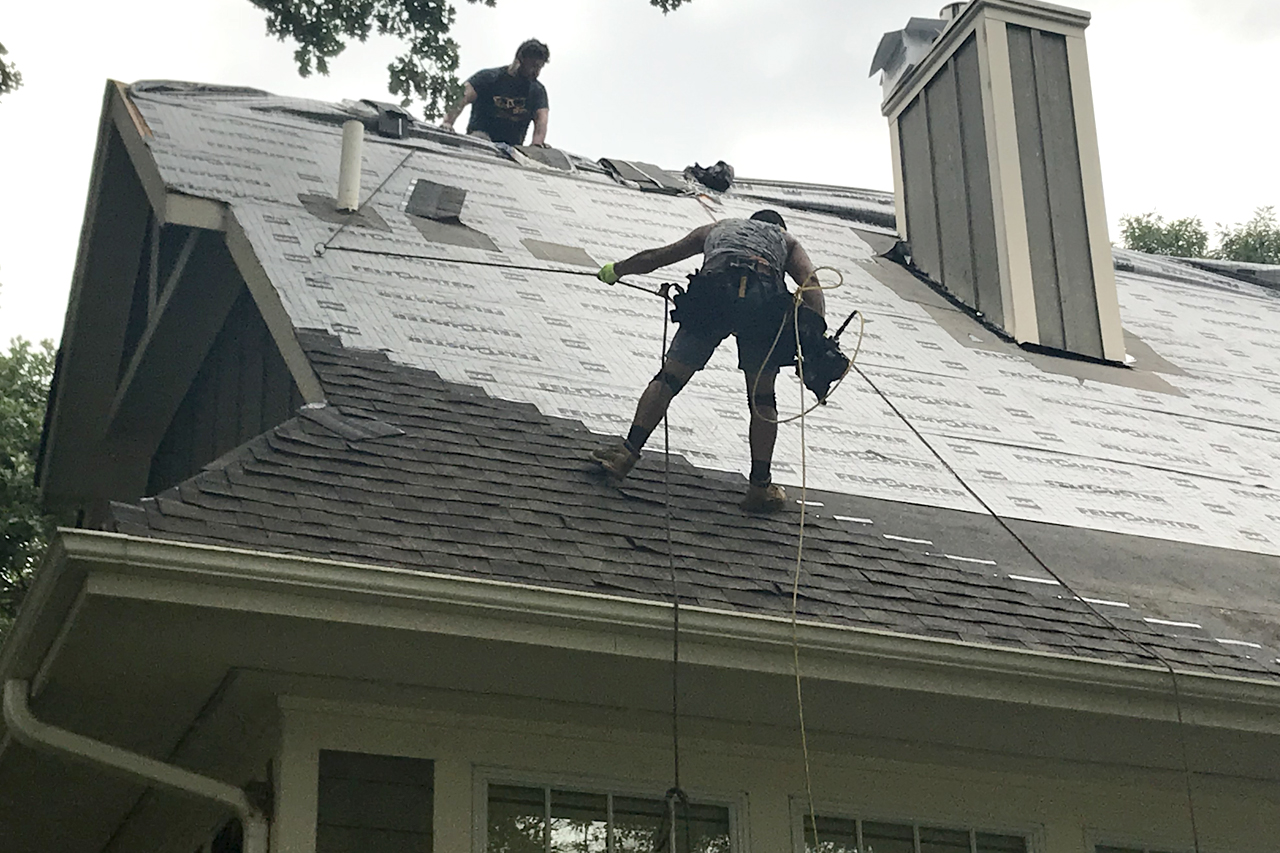 Picture of Two Men Working on Roof Adding New Shingles