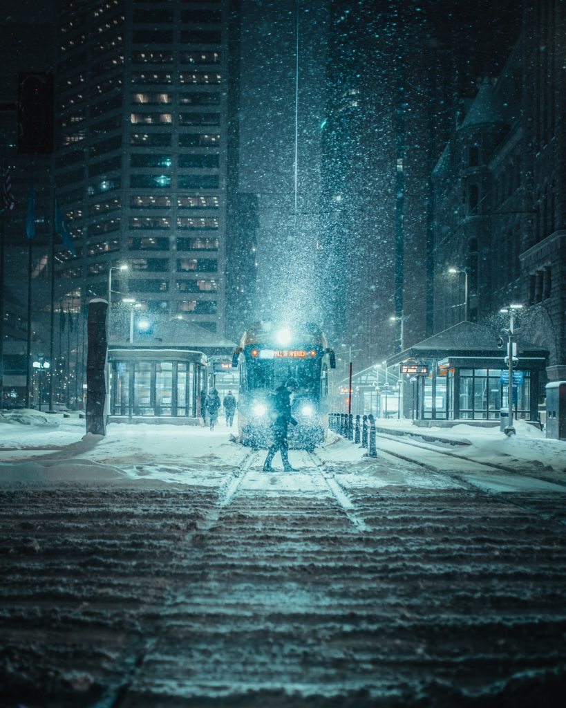 Picture of a person standing in Minneapolis as snow falls.